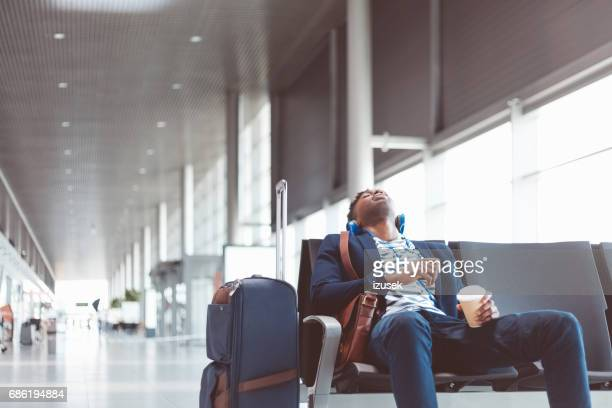 young traveler sleeping at airport waiting area - waiting stock pictures, royalty-free photos & images