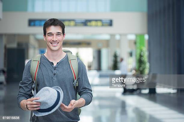Young traveler smiling at camera in departure terminal.