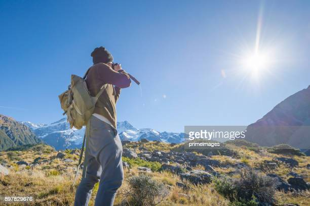 Young traveler taking photo at mt cook famaus destination in new zealand