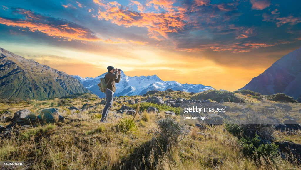 Young traveler taking photo at mt cook famaus destination in new zealand : Stock Photo
