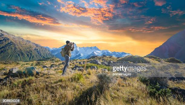 young traveler taking photo at mt cook famaus destination in new zealand - otago region stock pictures, royalty-free photos & images