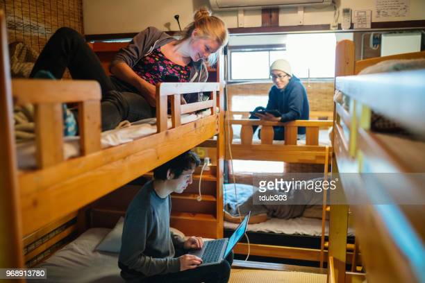 young travelers in a dormitory style backpacker's hostel using a laptop computer - hostel stock pictures, royalty-free photos & images