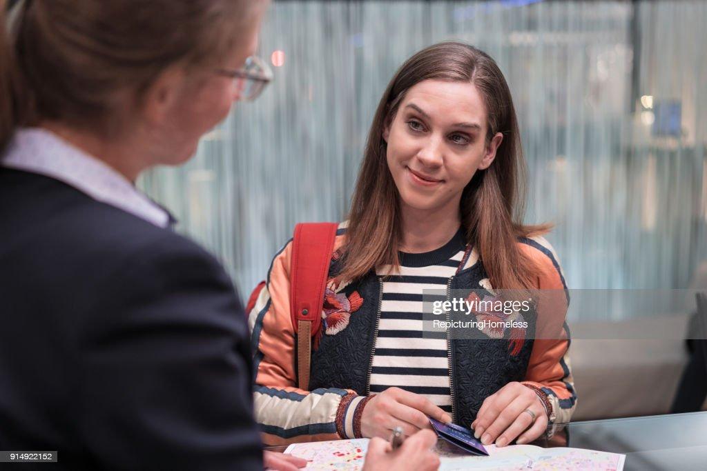 Junge Frau stellt der Rezeptionistin Fragen : Stock-Foto