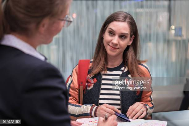 Junge Frau stellt der Rezeptionistin Fragen
