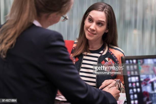 Junge Frau hört der Rezeptionistin aufmerksam zu
