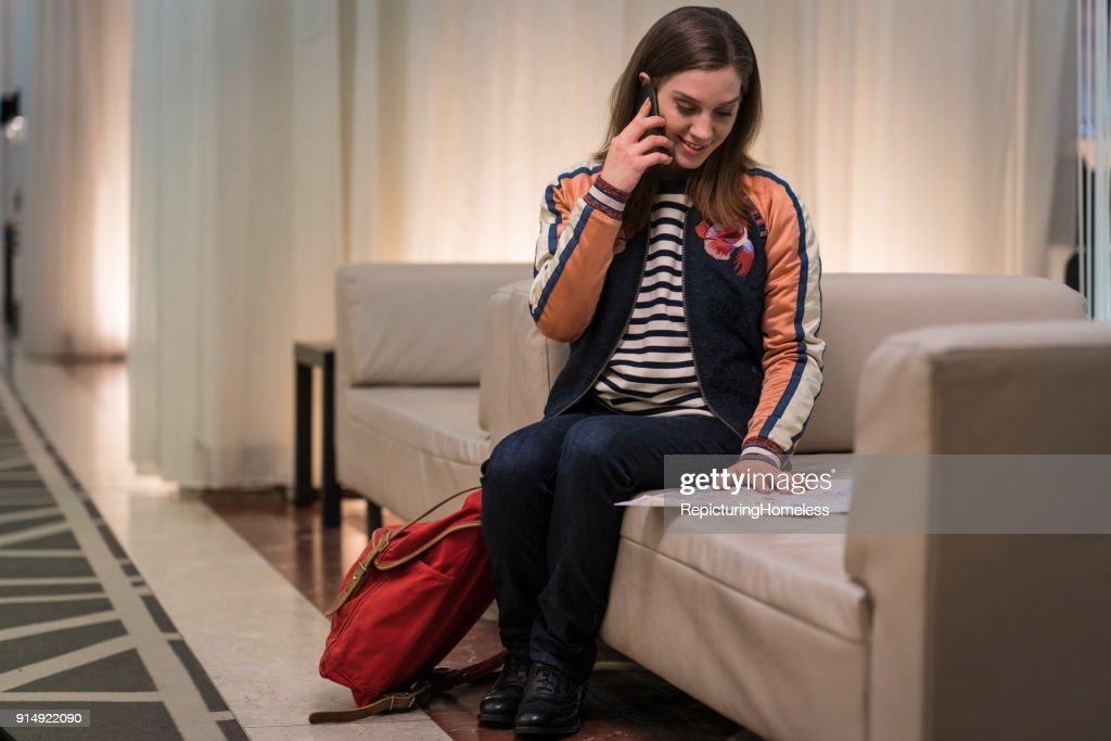 Junge Frau telefoniert und schaut sich eine Karte an : Stock-Foto