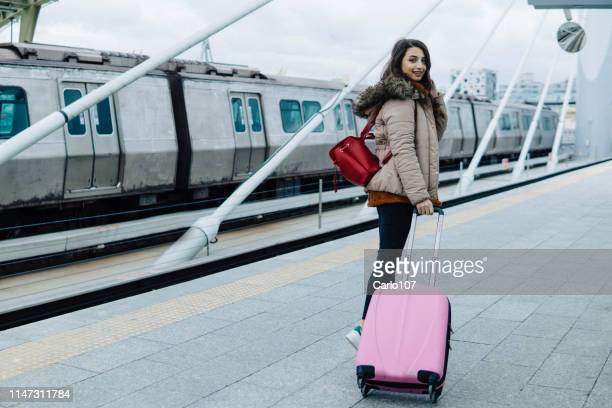 junge reisende mit ihrem koffer - bahnreisender stock-fotos und bilder