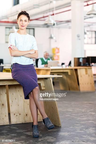 Joven empresario de moda con brazos cruzados apoyarse en escritorio