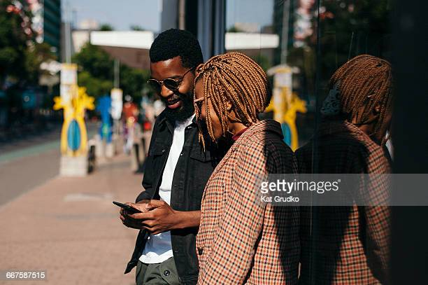 young trendy ethnic african couple on mobile device outside coffee shop in trendy street in braamfontein johannesburg south africa - downtown comedy duo stock pictures, royalty-free photos & images