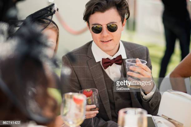 young trendy male drinking in a marquee - fascinator stock pictures, royalty-free photos & images