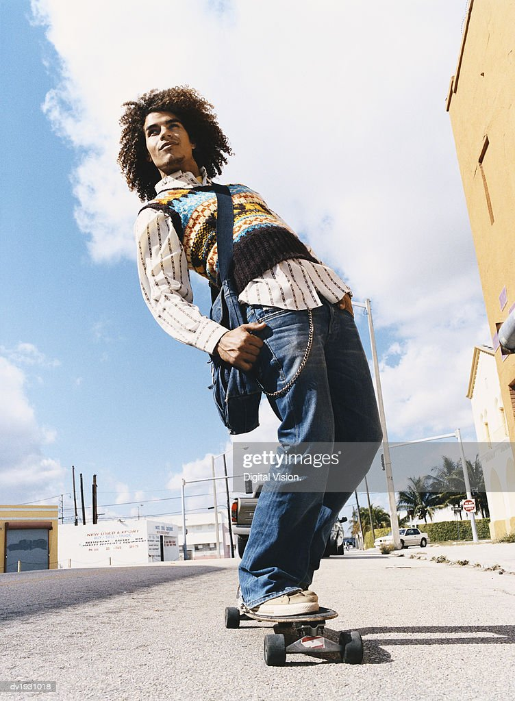 Young Trendy Man Riding Down the a Pavement on His Skateboard : Stock Photo