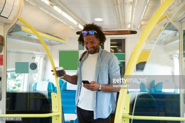 young trendy man smiling while using smart phone in train - train interior stock pictures, royalty-free photos & images