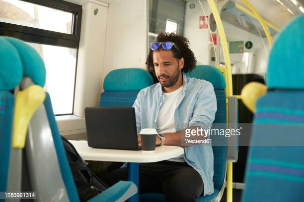 young trendy man using laptop in train - train interior stock pictures, royalty-free photos & images