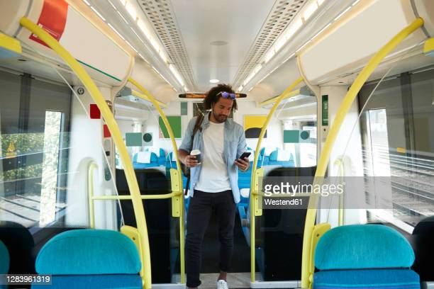 young trendy man using smart phone while standing in train - train interior stock pictures, royalty-free photos & images