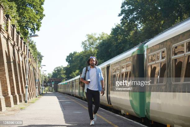 young trendy man walking at railroad station platform during sunny day - railway station stock pictures, royalty-free photos & images