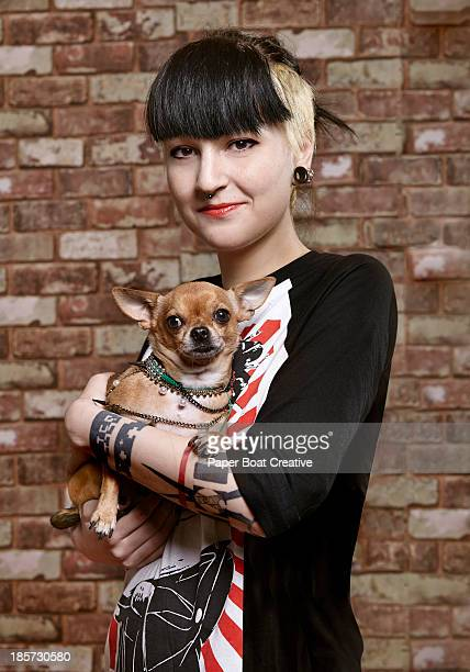 Young trendy student holding her pet dog