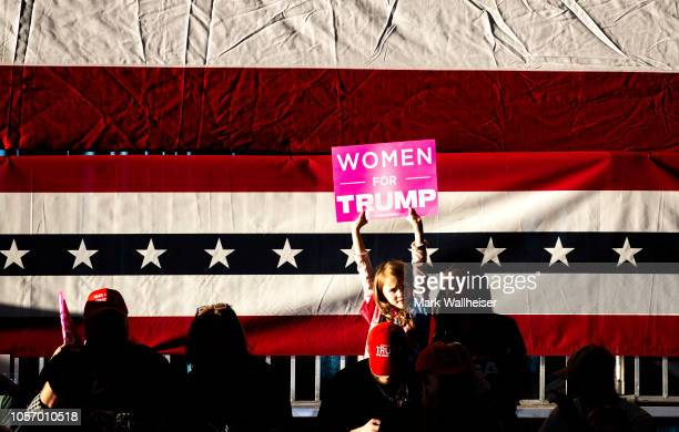 A young Trump supporter waves her sign while she waits to see US President Donald Trump at a campaign rally at the Pensacola International Airport on...