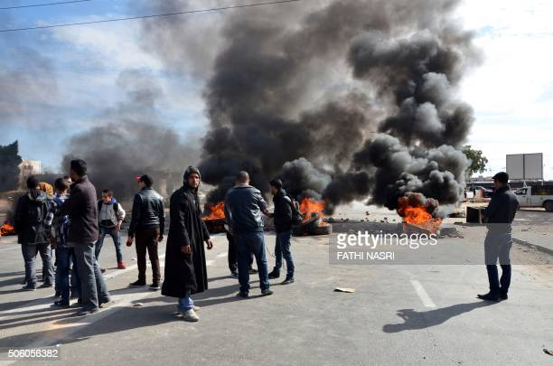 Young Tunisian graduates block the road with burning tyres in the south eastern town of Medenine on January 21 in solidarity with protests in the...