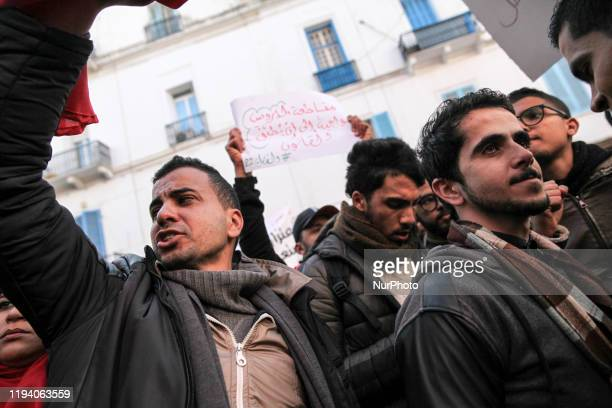 Young Tunisian men raise a placard while shooting slogans against the government as they attend a gathering held outside the UGTT labor union...