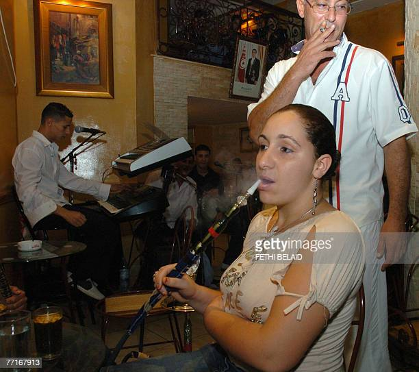 A young Tunisian woman smokes a water pipe known locally as narguileh or shisha at a cafe in Tunis in the early hours of 02 October 2007 During the...
