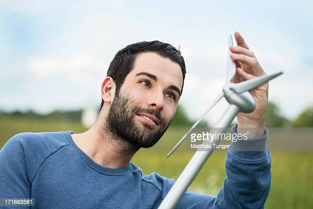 A young Turkish man looks at a wind turbines