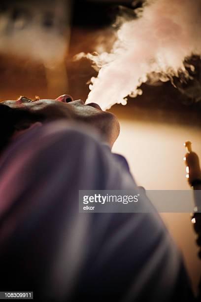 young turkish man smoking hookah. - hookah stock photos and pictures