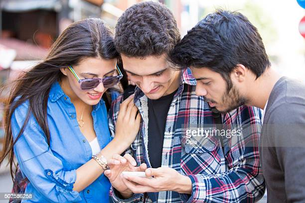 Young Turkish people looking at smart phone
