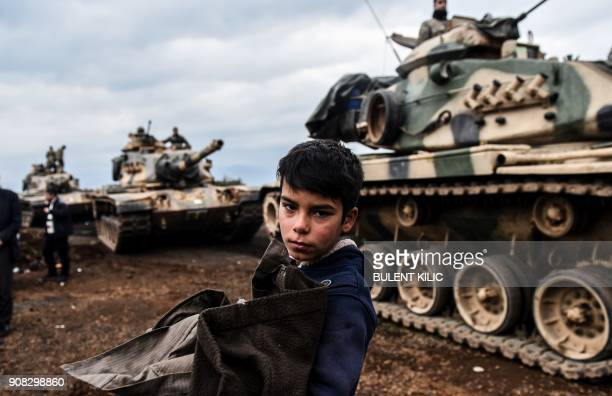 TOPSHOT A young Turkish villager stands next to Turkish army tanks as soldiers gather close to the Syrian border on January 21 2018 at Hassa in Hatay...