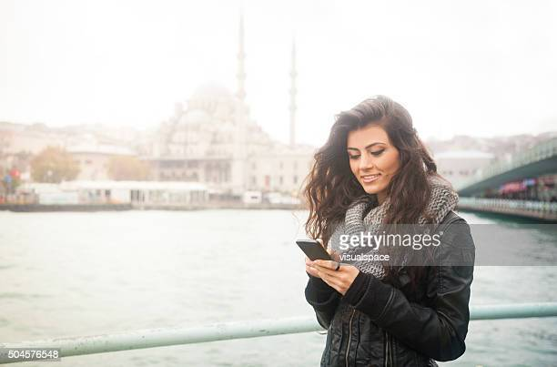 Young Turkish Woman Texting On Phone In Istanbul Near Water