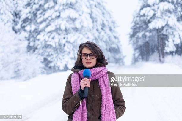 joven reportera de televisión en bosque del invierno - journalist fotografías e imágenes de stock