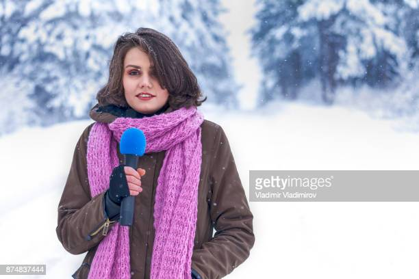 Young tv reporter in winter forest