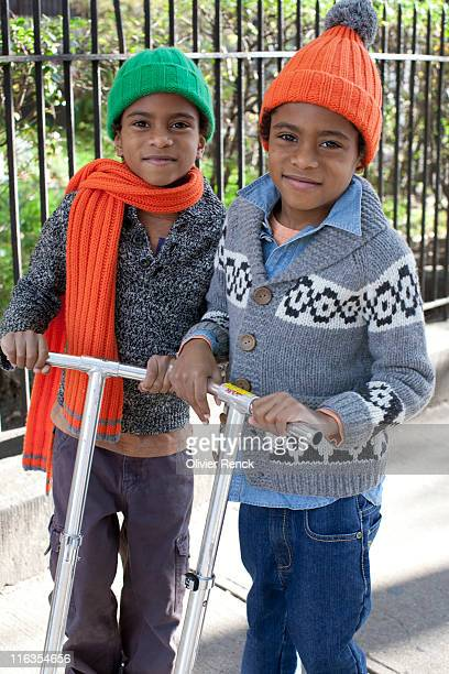 Young twin boys posing for a portrait while on their scooters in Harlem, New York.
