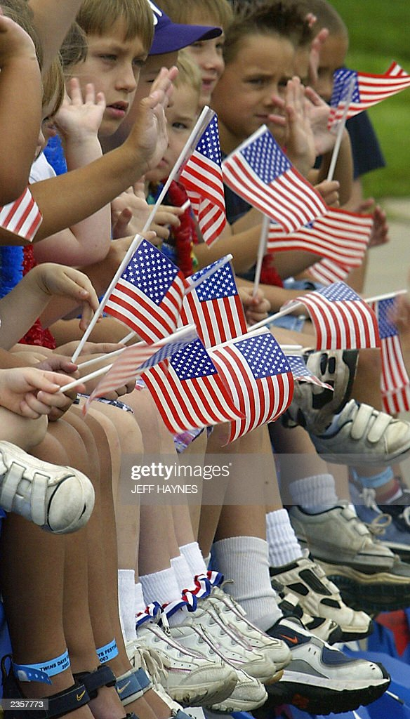 Young twins hold American flags as they ride in the 28th Twins Day Festival parade 02 August, 2003 in Twinsburg, Ohio. The event, billed as the 'Largest Annual Gathering of Twins in the World,' is the only festival where twins worldwide gather to celebrate being of multiple birth. AFP PHOTO/Jeff HAYNES