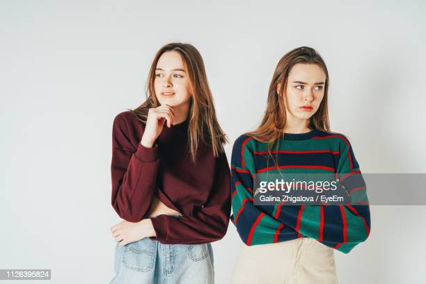 young twins standing against white background - 双子 ストックフォトと画像