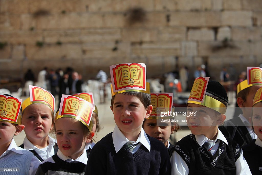 Young ultra-Orthodox Jewish boys wear paper crowns inscribed with a biblical prayer during a class trip to the Western Wall on February 2, 2010 in Jerusalem, Israel. The lower courses of the ancient stones of Judaism's holiest site are the last remaining vestiges of the Second Jewish Temple built by Herod the Great around 19 BC, while the upper half dates from the seventh century AD onwards.