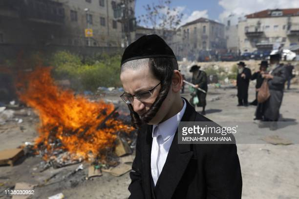 A young UltraOrthodox Jewish man passes in front of burning leavened items during the Biur Chametz ritual on April 19 2019 in Jerusalem on the eve of...