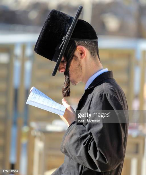 CONTENT] A young UltraOrthodox Jewish man praying at the Western Wall of Jerusalem at Tish'a B'av His hat is tilted down in front of his eyes so the...
