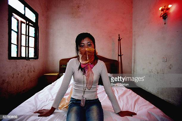 Young underage prostitute sits on a bed in a brothel November 25, 2004 in Cheng Du, China. Her face is covered due to her fear of repercussions if...