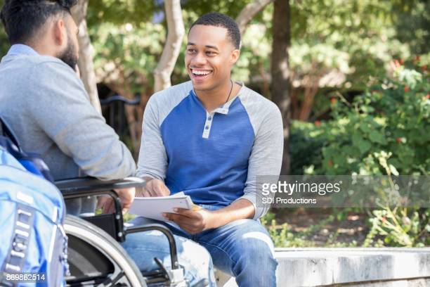 Young university student enjoys studying with wheelchair bound friend