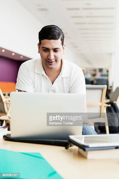 Young university student using laptop at table in library
