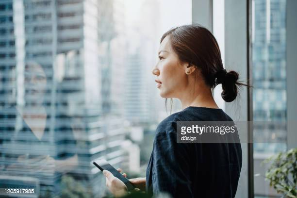 young urban businesswoman using smartphone in the office in front of windows overlooking the city - downtown stock pictures, royalty-free photos & images