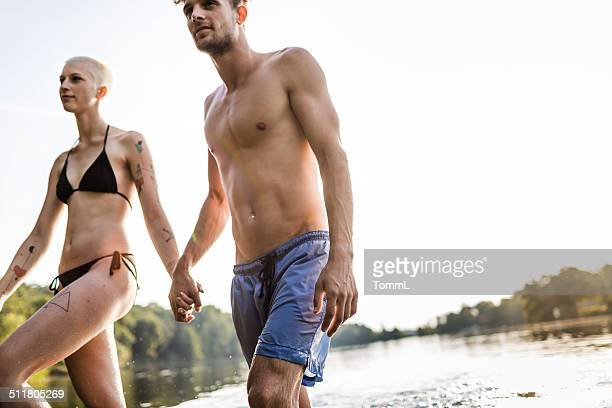 young urban couple holding hands at lake - german naturist stock pictures, royalty-free photos & images