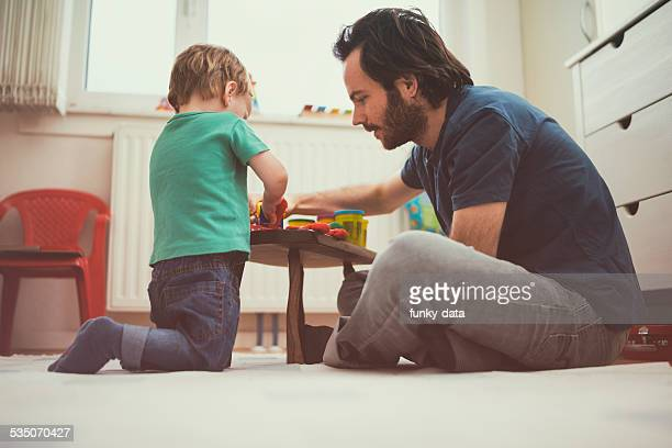 Young urban father playing with his toddler son