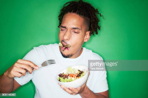 young urban man eating salad