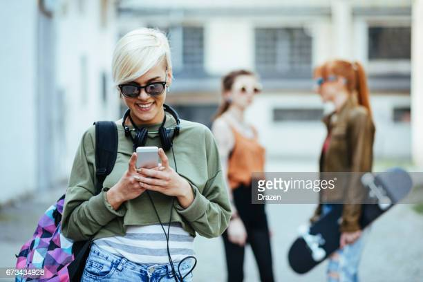 Young urban woman using phone for communication