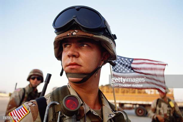 A young US marine arrives at Dhahran air base from the USA with his Stars and Stripes flag flying proudly from his helmet during the Gulf War...