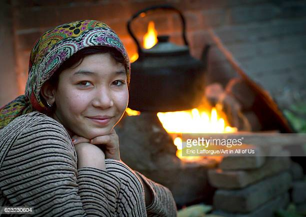 Young Uyghur woman and wood stove Kashgar Xinjiang Uyghur Autonomous Region China on September 24 2012 in Kashgar China