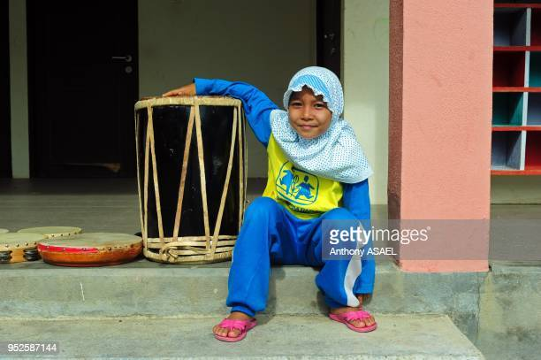 young veiled girl with SOS outfit playing the drums Banda Aceh Sumatra Indonesia