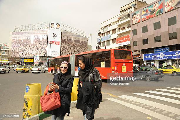Young veiled women fully covered in accordance with Islamic dress code walk in front of posters of Iran's leader Ayatollah Seyyed Ali Khamenei and...