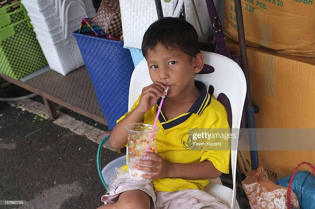 A young vendor boy drinks a soda shake with a straw while sat on a chair outside a shop in a busy market place on October 12, 2012 in Bangkok, Thailand.